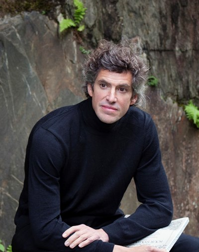 Head and upper body of pianist Richad Ormrod wearing black sleeved jumper seated with music in hand.